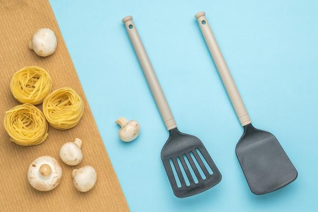 Pâtes, champignons et deux spatules de cuisine sur fond bleu. ingrédients pour faire des pâtes.