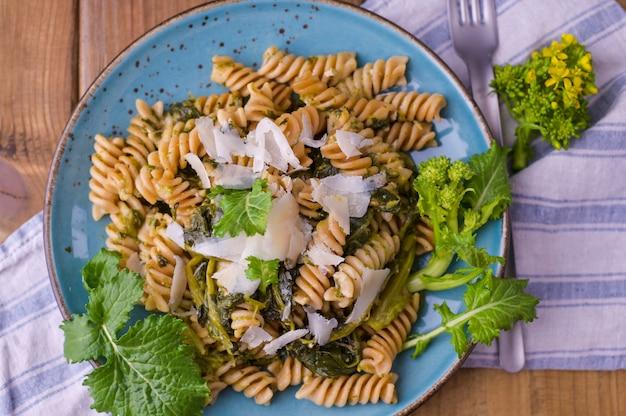 Pâtes cime di rapa dans une assiette avec du parmesan sur une table en bois. cuisine traditionnelle du sud de l'italie, des pouilles. photo de style rustique. espace copie