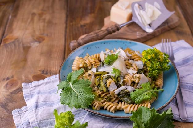 Pâtes cime di rapa dans une assiette avec du parmesan sur une table en bois. cuisine traditionnelle du sud de l'italie, des pouilles. photo de style rustique.