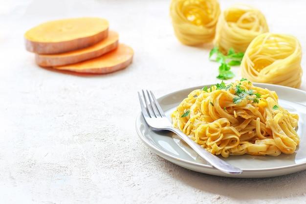 Des pâtes à la citrouille alfredo fettucine dans une assiette en céramique avec des tranches fraîches de courge musquée. repas d'automne pour le déjeuner. recette de courge musquée.