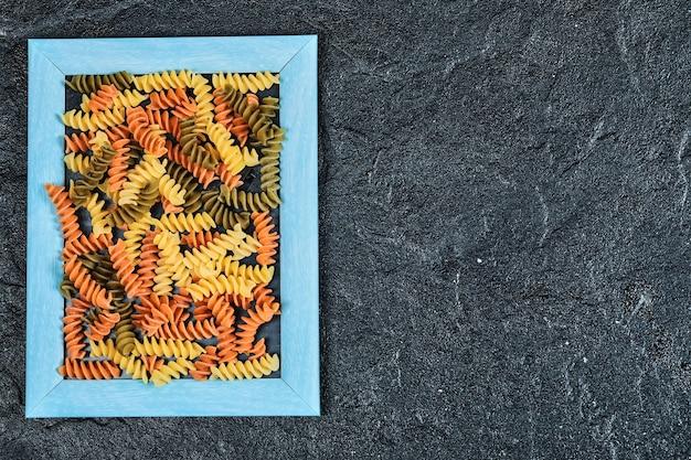 Pâtes colorées crues dans un cadre photo sur noir.
