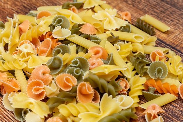 Pâtes colorées, macaroni, pâtes sur fond de bois close up selective focus