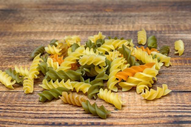 Pâtes colorées, spaghettis colorés, fusilli, macaroni sur fond de bois close up selective focus