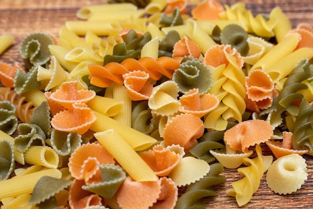 Pâtes colorées, spaghettis colorés, macaroni, pâtes sur fond de bois se bouchent