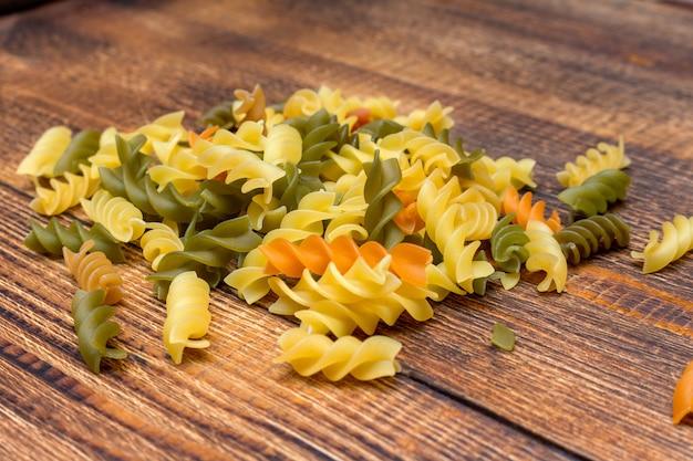 Pâtes colorées, spaghettis colorés, macaroni, pâtes sur fond de bois