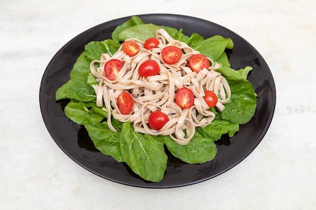 Pâtes complètes aux feuilles vertes de roquette et tomate cerise sur plaque noire et marbre blanc