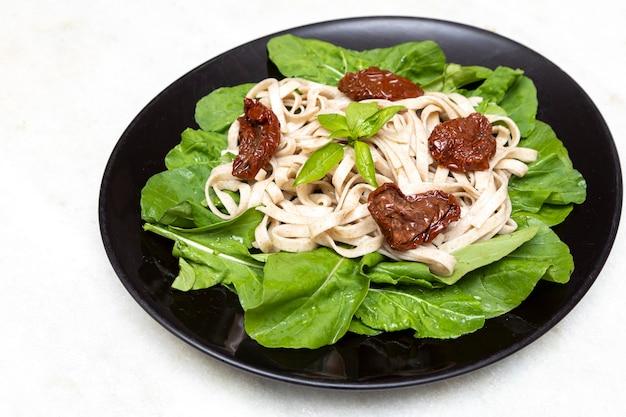 Pâtes complètes aux feuilles vertes de roquette et tomate séchée sur plaque noire et marbre blanc