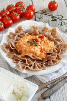 Pâtes complètes avec du fromage stracchino et des tomates fraîches close up