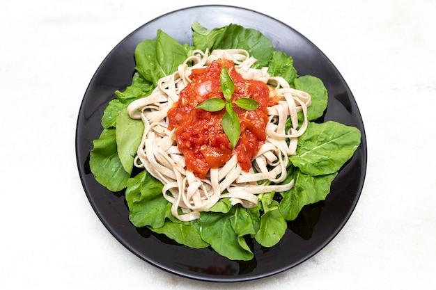 Pâtes complètes avec des feuilles vertes de roquette, sauce rouge et vinaigre balsamique sur plaque noire et fond de marbre blanc