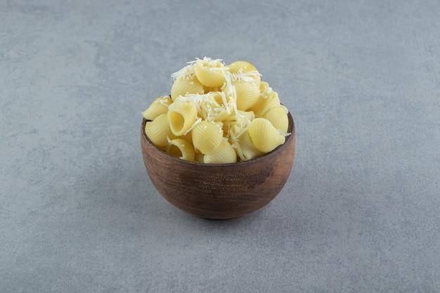 Pâtes conchiglie bouillies dans un bol en bois.