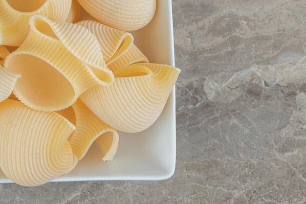 Pâtes conchiglie non cuites dans un bol blanc