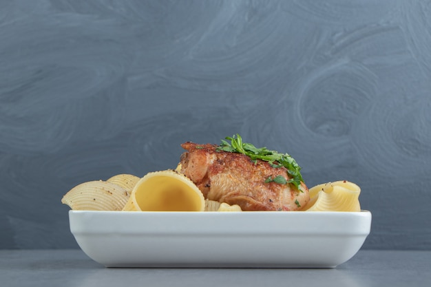 Pâtes conchiglie et poulet grillé sur plaque blanche.