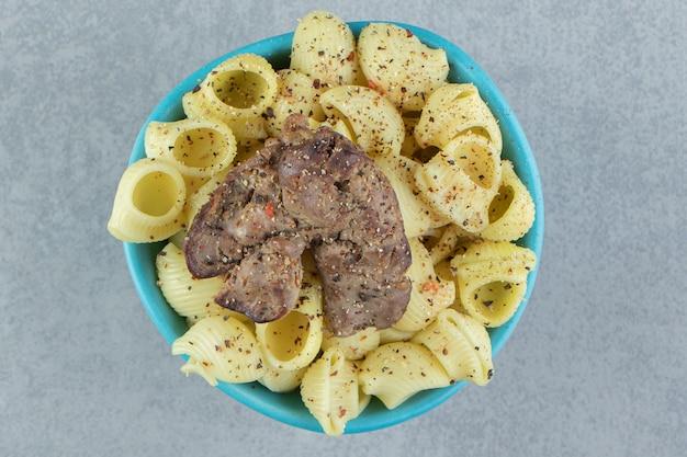 Pâtes conchiglie et viande frite dans un bol bleu.