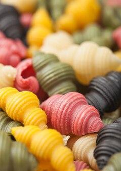 Pâtes conchiglioni tricolore crues fraîches comme fond de texture. macro
