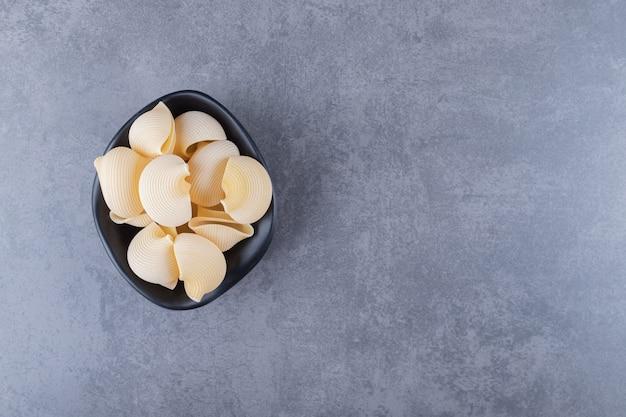Pâtes de coquillage crues dans un bol noir.