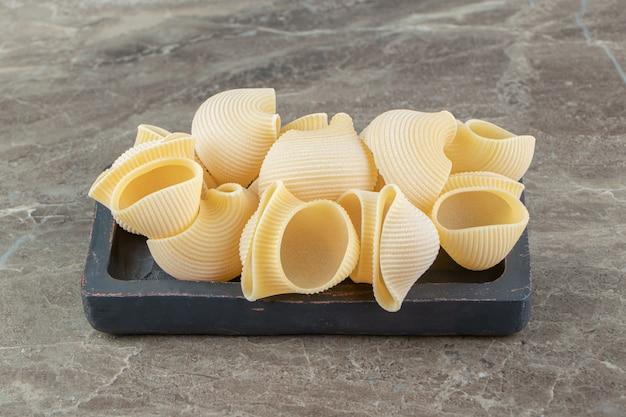 Pâtes de coquillage non cuites sur plaque noire