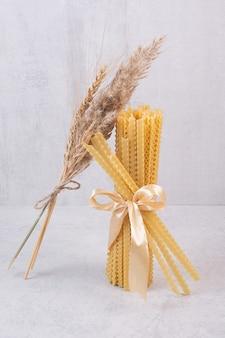 Pâtes crues attachées avec un ruban sur une surface blanche