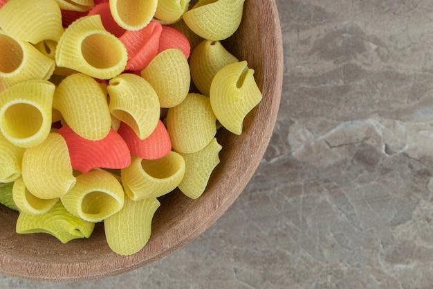 Pâtes crues de conchiglie dans la cuvette en bois