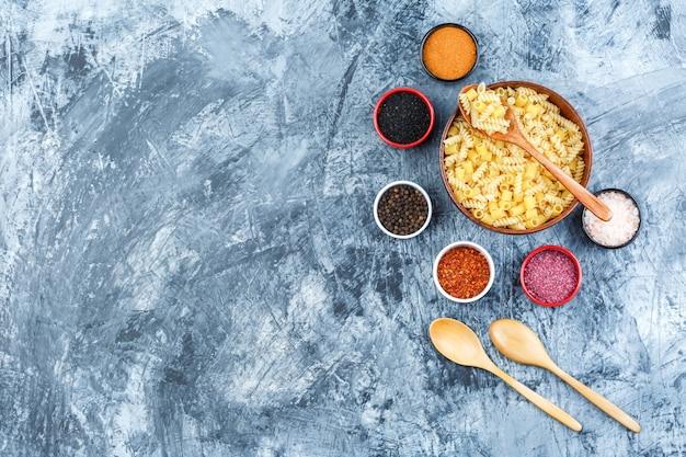 Pâtes crues dans un bol d'épices, cuillères en bois vue de dessus sur un fond de plâtre gris