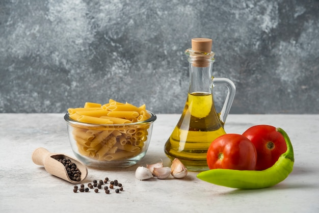 Pâtes crues dans un bol en verre, bouteille d'huile d'olive, grains de poivre et légumes sur tableau blanc.