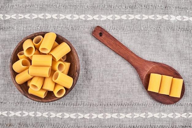 Pâtes crues dans une cuillère en bois et dans une tasse sur une surface grise.