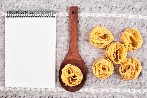 Pâtes crues dans une cuillère en bois avec un livre de recettes.