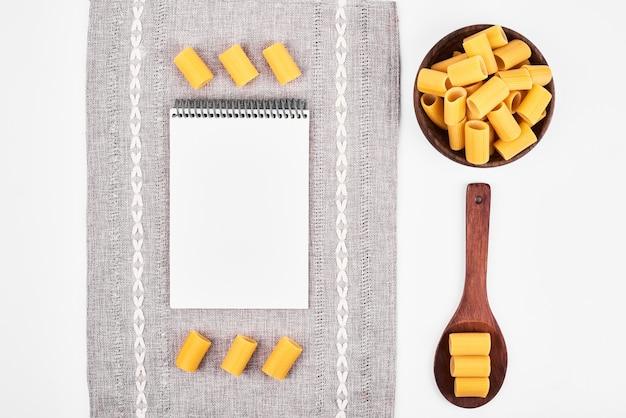 Pâtes crues dans des cuillères en bois sur fond blanc avec un livre de recettes.