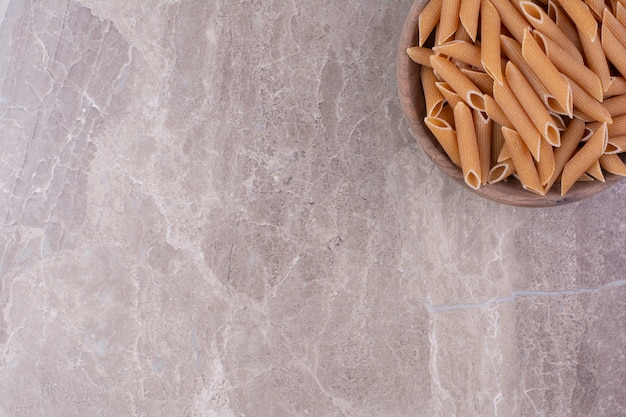 Pâtes crues dans une tasse en bois rustique sur espace gris.