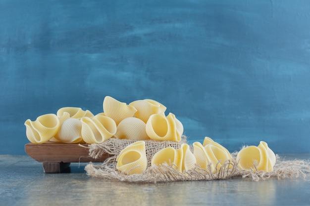 Pâtes crues sur dessous de plat, sur la surface en marbre.