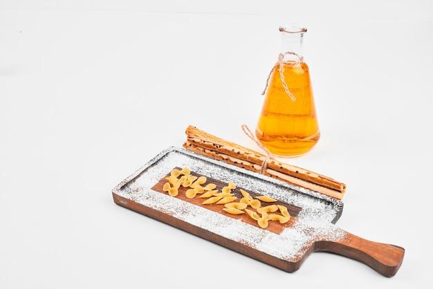 Pâtes crues dispersées sur planche de bois avec une bouteille d'huile et des craquelins sur blanc