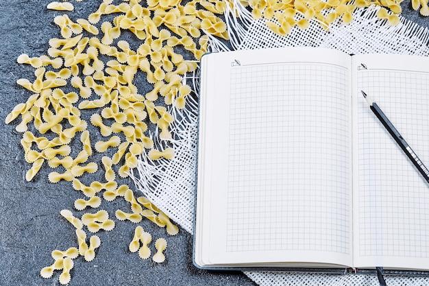 Pâtes crues éparpillées autour d'un cahier et d'un crayon avec une nappe blanche.