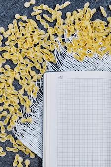 Pâtes crues éparpillées autour du cahier et de la nappe blanche.
