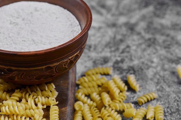 Pâtes crues éparpillées sur une table en marbre avec un bol de farine.