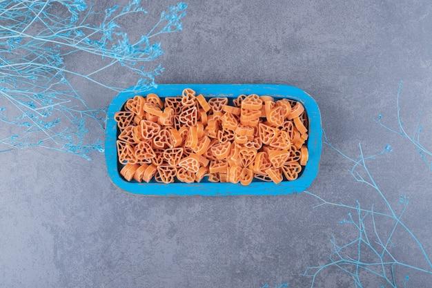 Pâtes crues en forme de coeur sur plaque bleue.