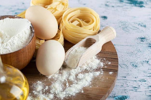 Pâtes crues avec de l'huile, des œufs et un bol de farine sur une planche de bois.