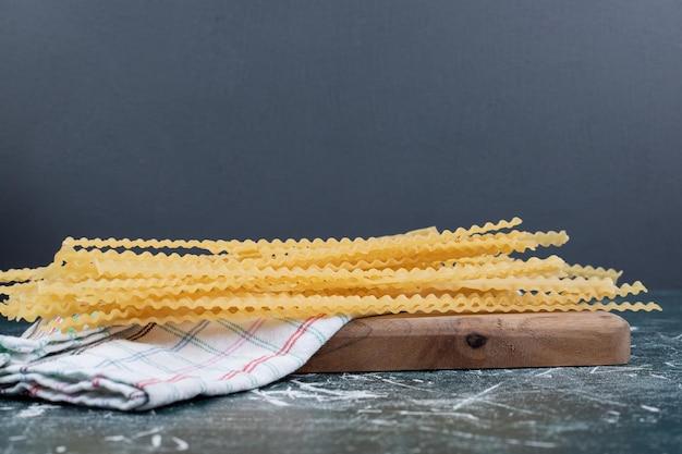 Pâtes crues jaunes avec nappe sur planche de bois.