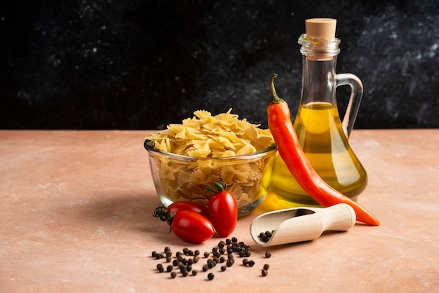 Pâtes crues, légumes et bouteille d'huile sur table orange.