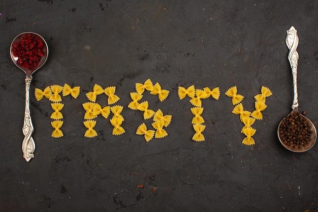 Pâtes crues mot savoureux en forme de jaune avec deux cuillères en argent avec différentes épices sur un bureau sombre