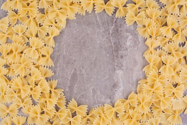 Pâtes crues et non cuites isolées sur la surface en marbre
