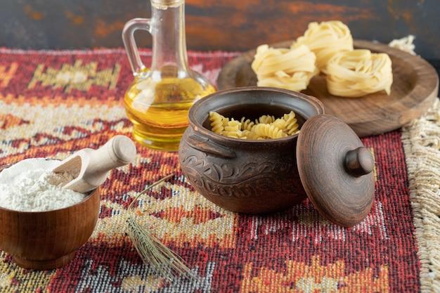Pâtes crues en spirale en pot avec macaronis crus fettuccine