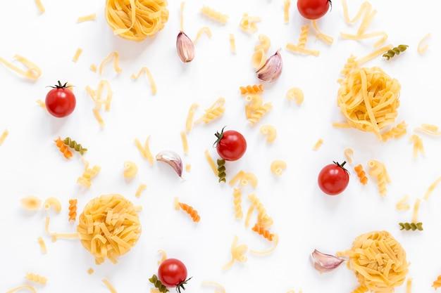 Pâtes crues et tomates cerises fraîches sur une surface blanche