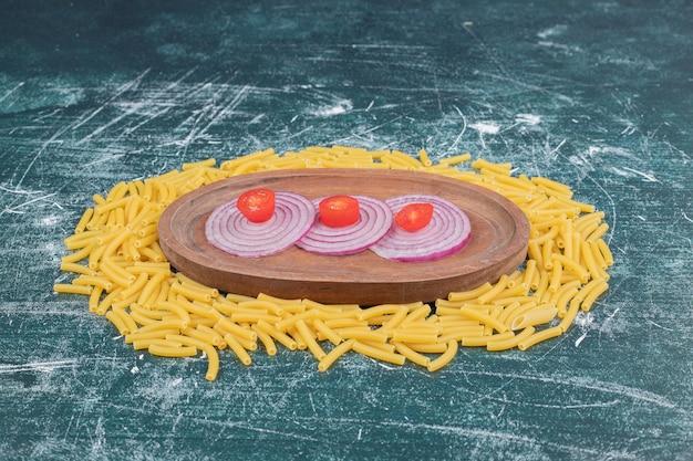 Pâtes crues avec des tranches d'oignon et une petite tomate sur un espace en marbre.