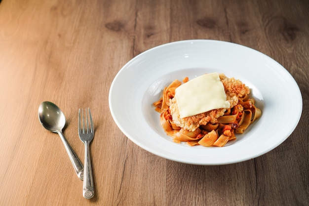 Pâtes, cuisine italienne, garniture de sauce tomate avec une escalope de porc croustillant frit et une feuille de fromage dans un plat blanc sur une table en bois brun foncé