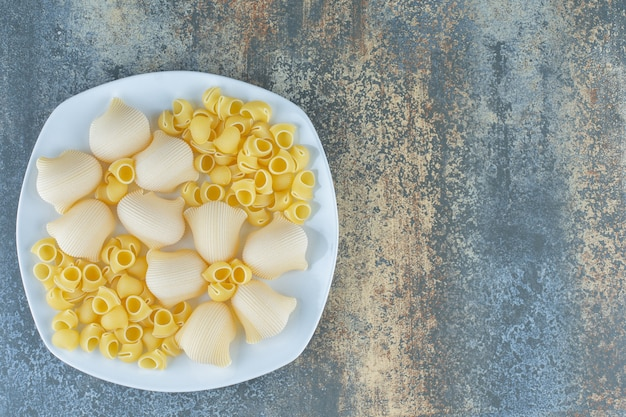 Pâtes cuites et non cuites dans le bol, sur le fond de marbre.