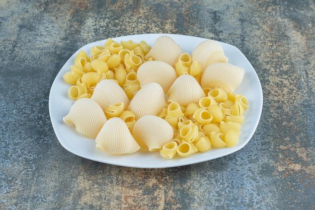 Pâtes cuites et non cuites dans le bol, sur la surface en marbre.
