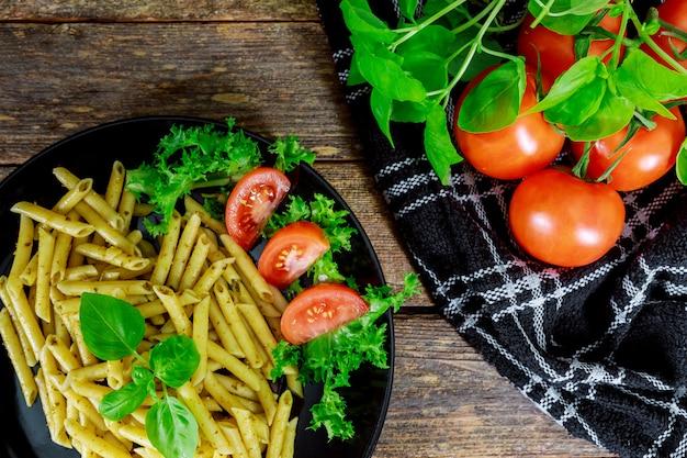 Pâtes cuites avec des tomates, du basilic et des légumes frais.