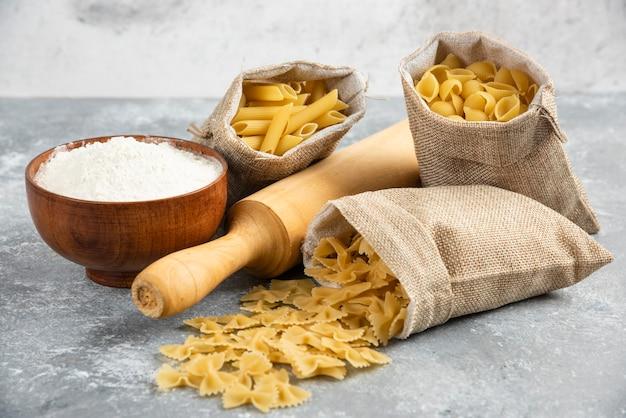 Pâtes dans un panier rustique avec rouleau à pâtisserie et une tasse de farine en bois autour.