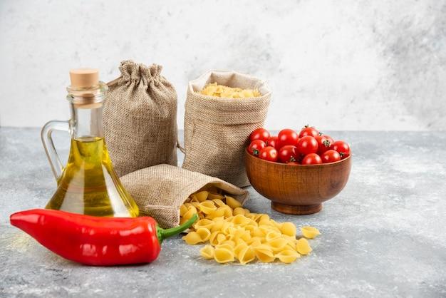 Pâtes dans des sacs rustiques servies avec des tomates cerises, des piments et de l'huile d'olive.