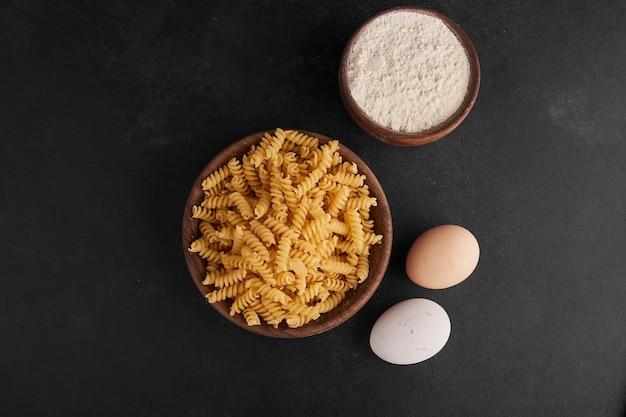 Pâtes dans une tasse en bois avec des ingrédients autour.
