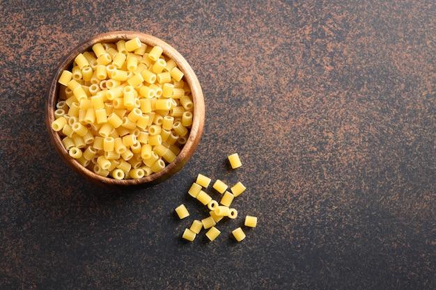 Pâtes ditalini dans un bol en bois sur table marron.